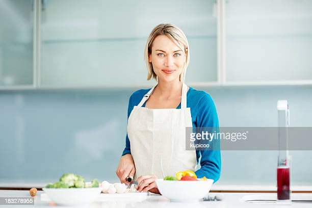 pretty, young woman chopping vegetables in the kitchen - apron stock pictures, royalty-free photos & images
