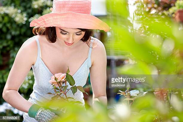 Pretty young woman cutting roses in garden