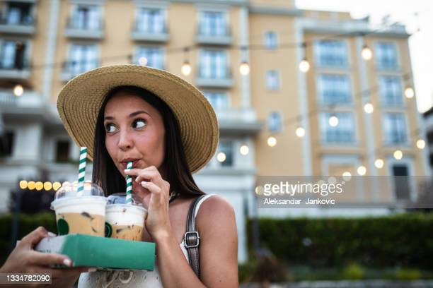 a pretty young woman drinking iced coffee through a straw - ambient light stock pictures, royalty-free photos & images