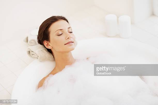 Pretty young woman enjoying bubble bath