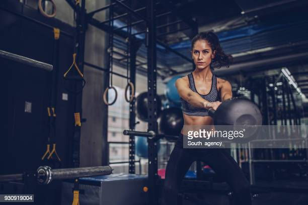 hübsche junge frau im fitness-studio trainieren - kugelhantel stock-fotos und bilder