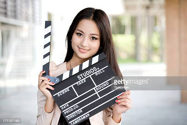 Pretty young woman holding a clapper