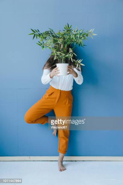 pretty young woman holding potted plant in front of her face - pot plant stock pictures, royalty-free photos & images