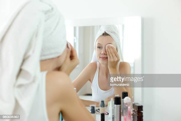 pretty young woman is cleaning her face - absence stock pictures, royalty-free photos & images