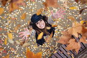 Pretty young woman looking to the sky with arms raised as leaves fall from the trees in the park in autumn.