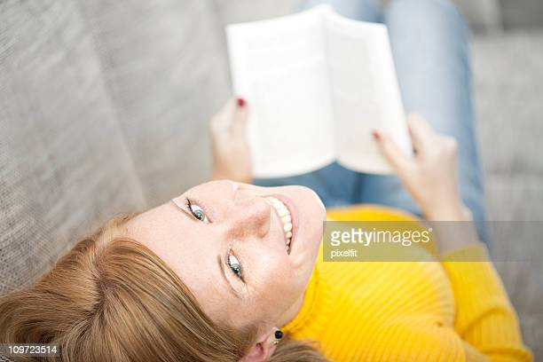 Pretty young woman lying on couch and smiling