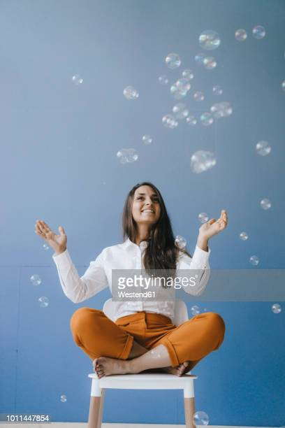 pretty young woman playing with soap bubbles - effortless stock pictures, royalty-free photos & images