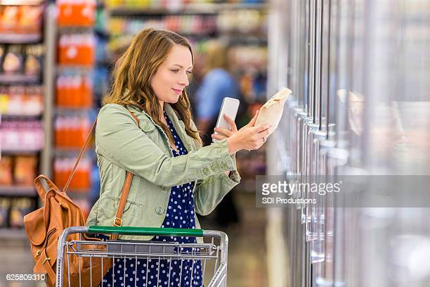 Pretty young woman reads label in grocery store aisle