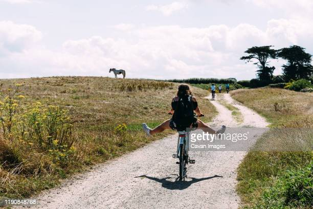 pretty young woman riding bicycle with open legs in a country road - scène rurale photos et images de collection