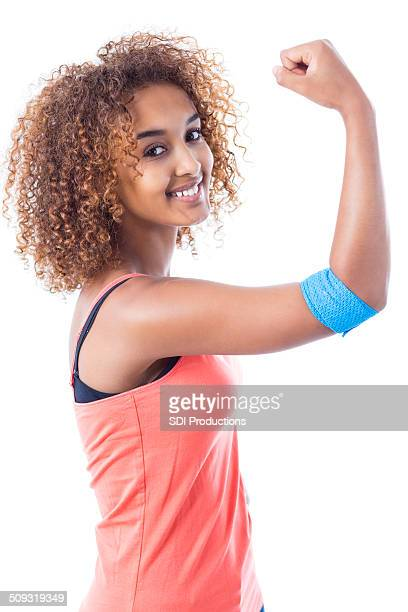 Pretty young woman showing muscles and bandage after donating blood