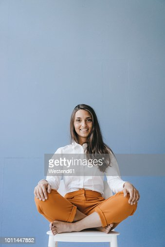 Pretty Young Woman Sitting Cross Legged On A Chair Stock