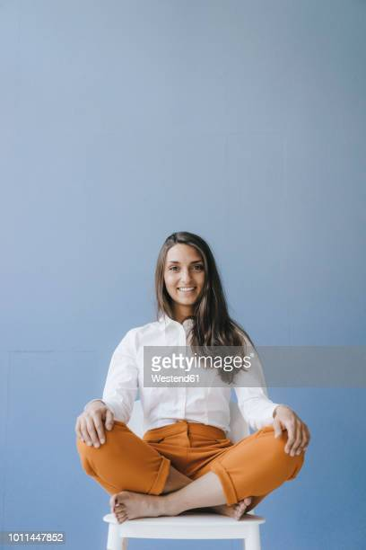 pretty young woman sitting cross legged on a chair - sitting foto e immagini stock
