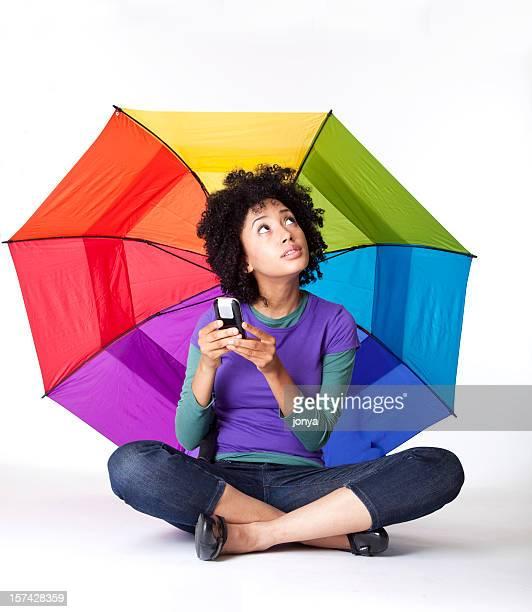 Bastante Joven mujer sentada con las piernas cruzadas bajo una sombrilla, SMS