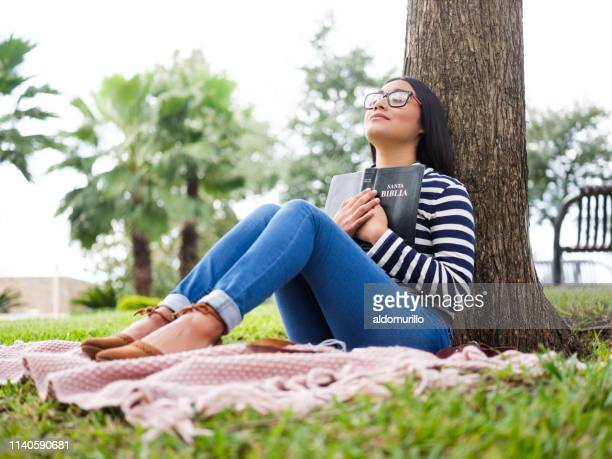 pretty young woman sitting next to tree and holding bible - religion stock pictures, royalty-free photos & images