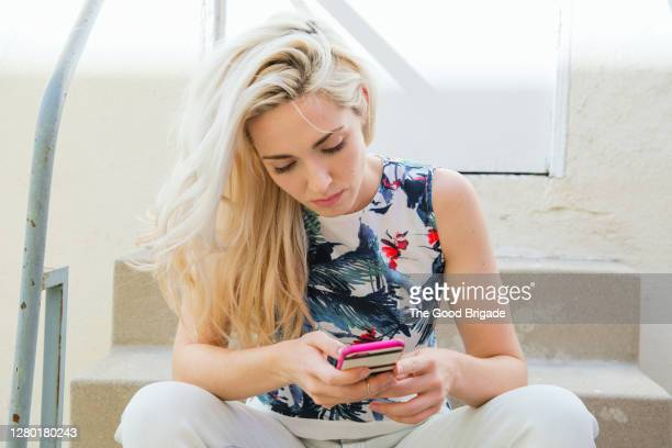 pretty young woman sitting  on stoop texting with smartphone - blonde hair stock pictures, royalty-free photos & images