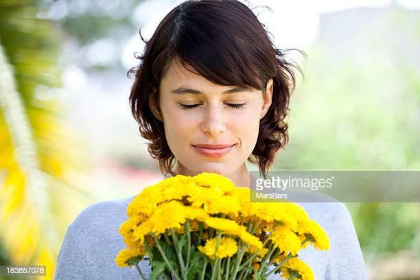 Hübsche Junge Frau riechen Blumen