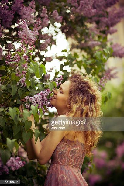 Pretty Young Woman Smelling Lilac in the evening