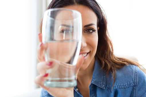 Pretty young woman smiling while looking at the camera through the glass of water at home. 1125744251