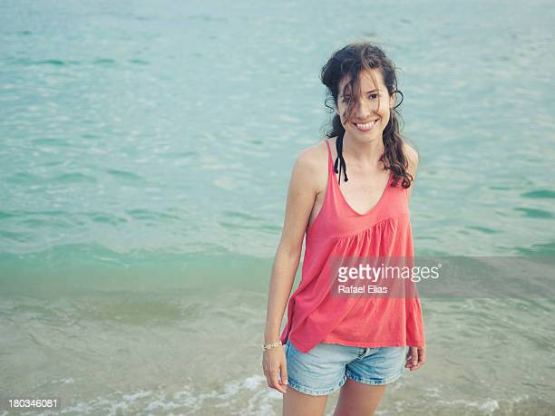 Pretty young woman standing on the shore