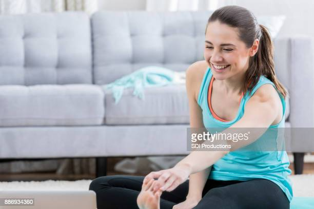 Pretty young woman stretches before working out