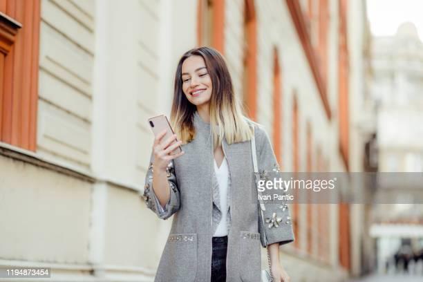 jolie jeune femme utilisant un téléphone - bonne nouvelle photos et images de collection