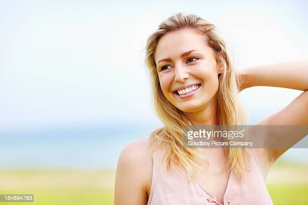 Pretty, young woman with hand behind head smiling