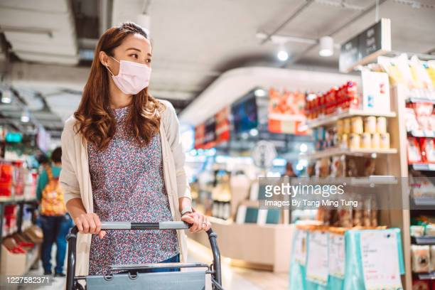 pretty young woman with medical face mask shopping for daily necessities and groceries in supermarket - パンデミック ストックフォトと画像