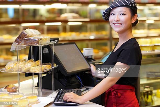 Jolie jeune femme travaillant dans la boulangerie