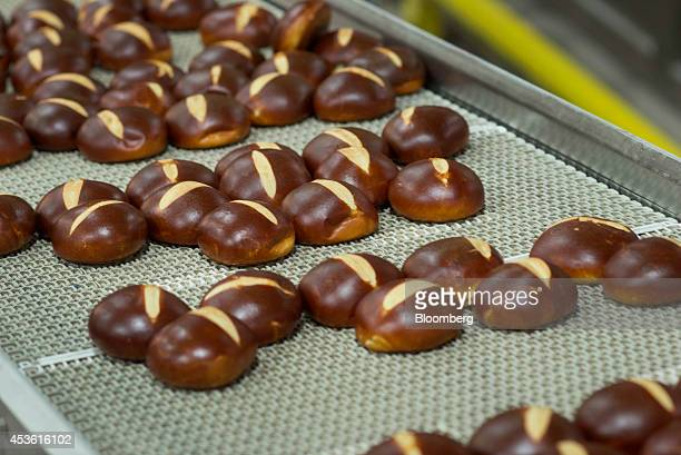 Pretzel Rolls cool on a belt before moving to the packaging area at the Orlando Baking Co in Cleveland Ohio US on Wednesday Aug 13 2014 Wheat rose...