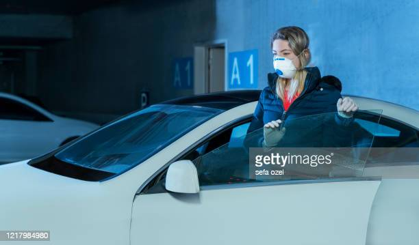 covi̇d-19 prevention in parking - driving mask stock pictures, royalty-free photos & images