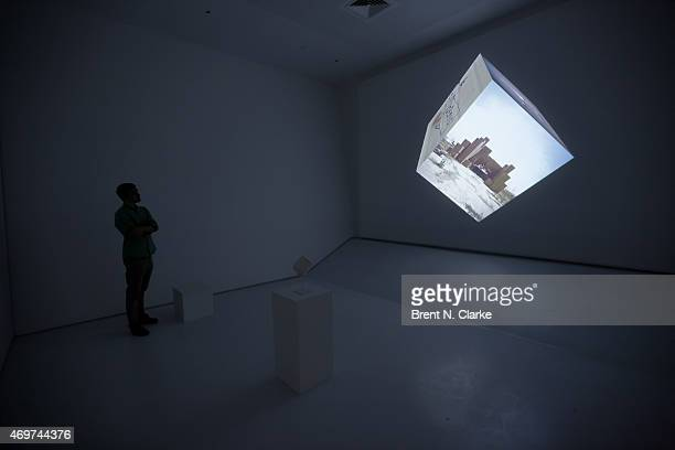 A preview attendee explores an interactive film exhibit entitled Google CubeUntitled during the Sensory Stories Press Preview held at the Museum of...