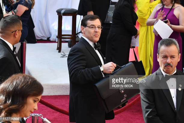 A PricewaterhouseCooper representative carrying the awards envelopes arrives for the 91st Annual Academy Awards at the Dolby Theatre in Hollywood...