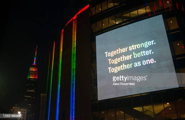A pride colored Madison Square Garden displays a digital screen that reads Together stronger Together better Together as one in rainbow colors near a...