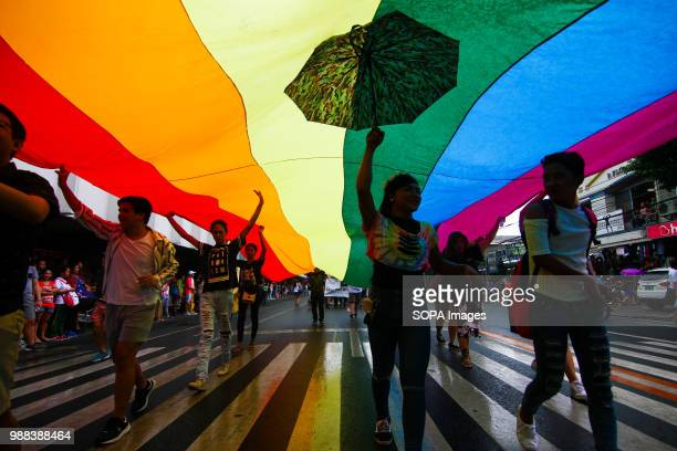 Pride march participants hold a rainbow flag during the parade. Thousands of gay members marched through the streets of Marikina, Metro Manila as...