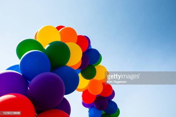 pride rainbow ballons arch horizontal with sky - pride stock pictures, royalty-free photos & images