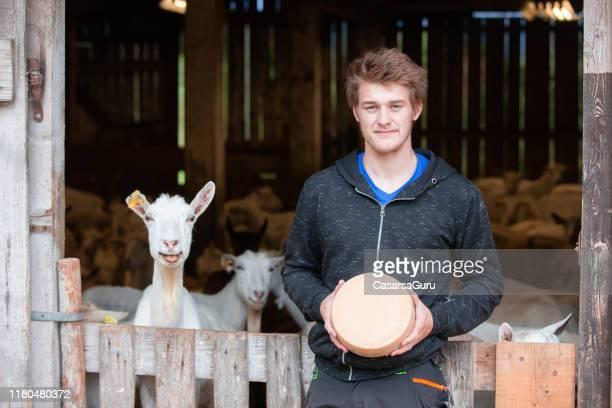 trots jonge boer houden een geit hele kaas ronde - kaas stockfoto's en -beelden