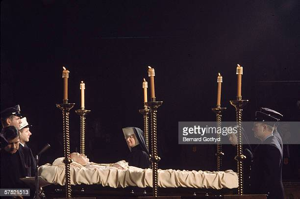 A priest adjusts a microphone stand as nuns pass by the corpse of American Roman Catholic archbishop and cardinal Francis Spellman which lies in...