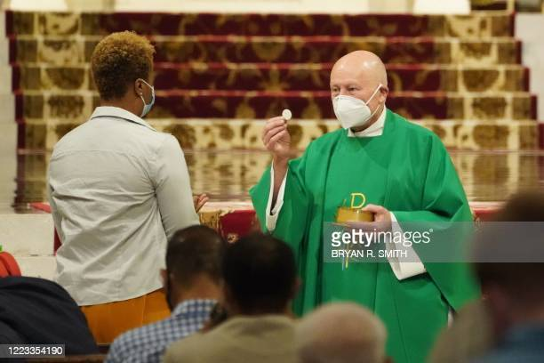 Priest administers communion to parishioners inside St. Patrick's Cathedral as it re-opens for Mass at 25% capacity amid the coronavirus pandemic on...