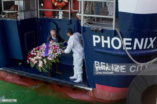 A priest and a crewmember from the Migrant Offshore Aid Station lay a wreath for the 34 migrants that drowned at sea attempting to reach Italy on May...
