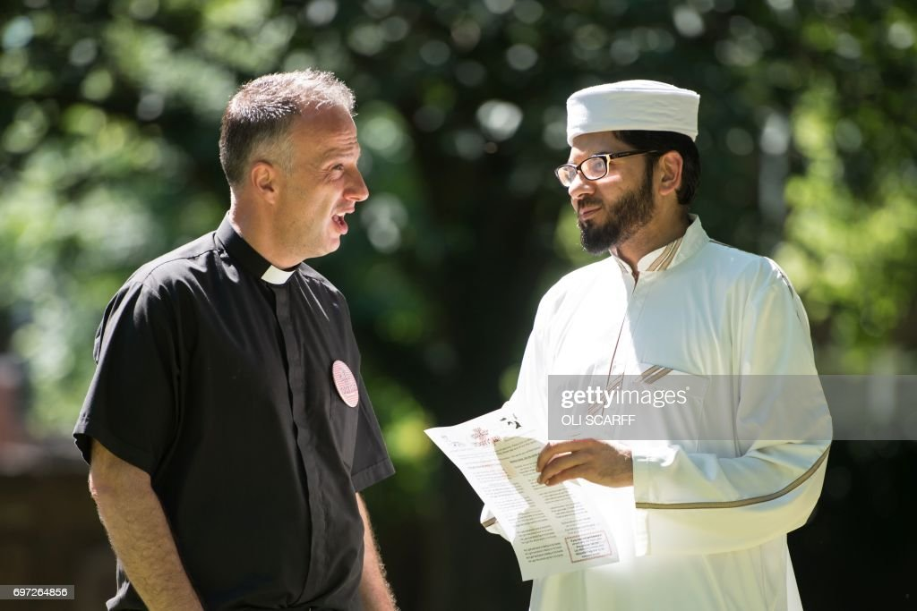 A priest and an imam chat before addressing members of the public at a 'Great Get Together' community service and picnic in memory of murdered Member of Parliament Jo Cox, marking the first anniversary since her killing, in the grounds of All Saints Church in Batley, northern England on June 18, 2017. The Great Get Together weekend is Inspired by murdered Labour MP Jo Cox's belief that we have more in common than which divides us, a line from her first speech to Parliament, and is a community initiative designed to unite people and communities on the streets and parks of their neighbourhoods. The 41 year-old Labour Party MP, Jo Cox, was assassinated by a pro-Nazi sympathiser in a terror attack in her constituency in northern England on June 16, 2016. /