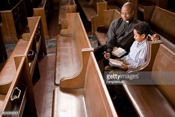 priest and boy in church pew reading bible - priest stock pictures, royalty-free photos & images
