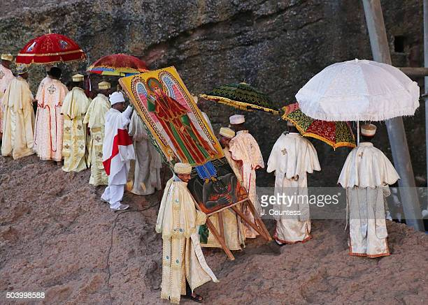 Priest and deacons march in a processional around Beta Mariam Church carrying an icon of Saint Michael on January 8 2016 in Lalibela Ethiopia...