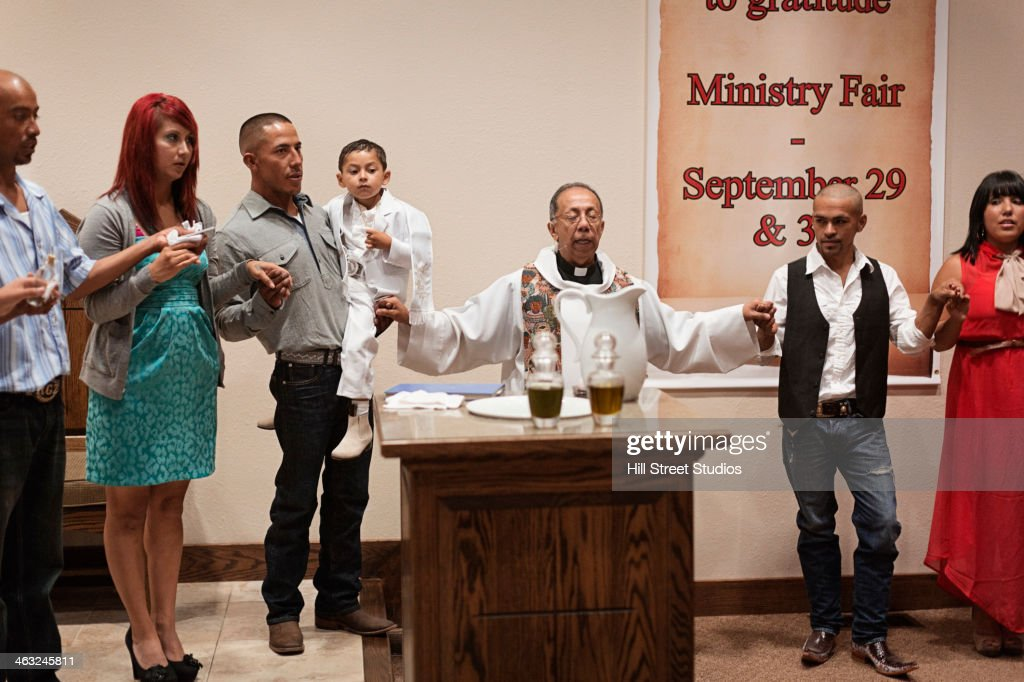 Priest And Family Praying Together At Baptism In Church Stock Photo