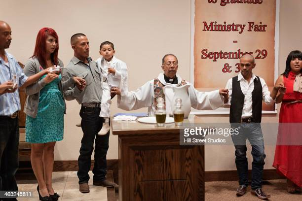 priest and family praying together at baptism in church - peettante stockfoto's en -beelden