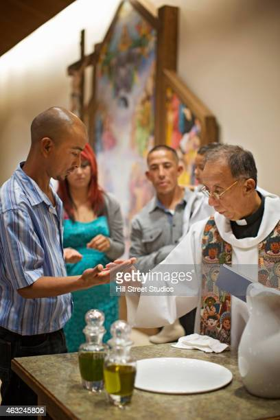 priest and man performing baptismal rites in church - catholic baptism stock pictures, royalty-free photos & images
