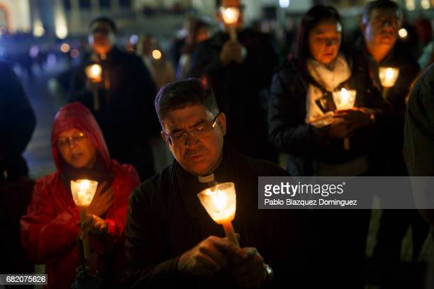 A priest and worshippers hold candles during a night mass in the Sanctuary of Fatima on May 11 2017 in Fatima Portugal Pope Francis will be attending...