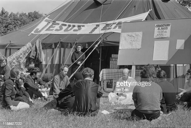Priest and worshippers outside the 'Jesus Tent' at the Glastonbury Fair music festival, 22nd - 26th June 1971. A sign offers mass and holy communion...