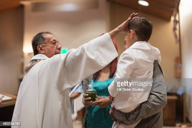 priest anointing boy in church - katholicisme stockfoto's en -beelden