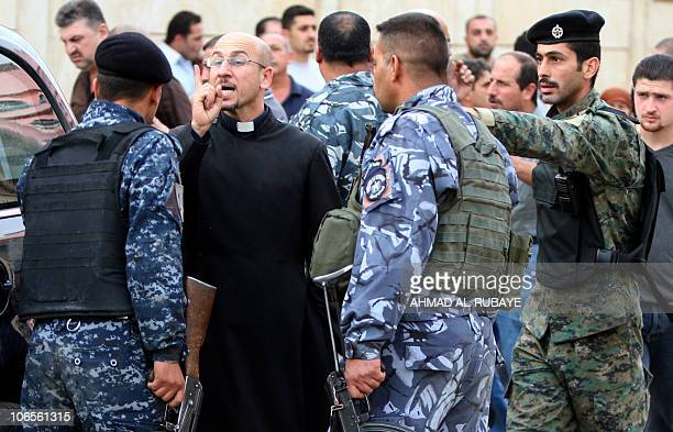 A priest argues with Iraqi security as he tries to enter the Sayidat alNejat Syrian Catholic cathedral in central Baghdad on November 1 where 46...