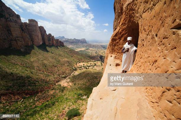 priest at the entrance of abuna yemata guh, tigray, ethiopia - tigray stock photos and pictures